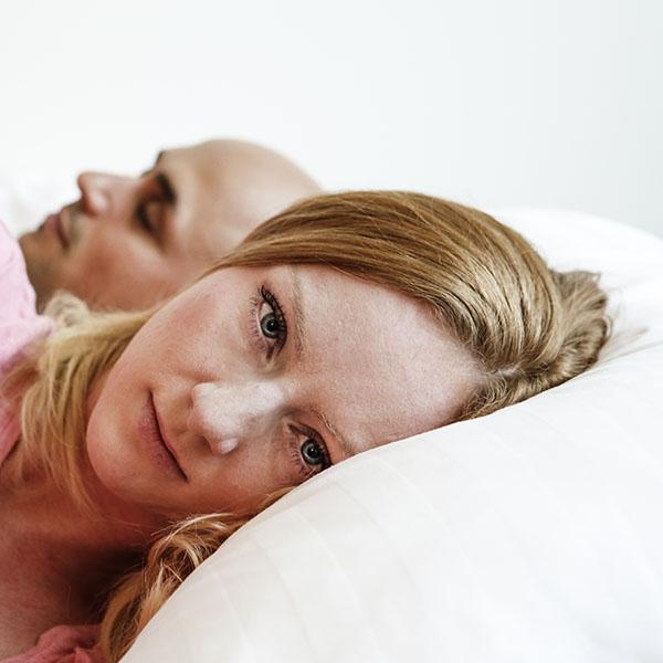 Frau liegt wach neben schlafendem Partner