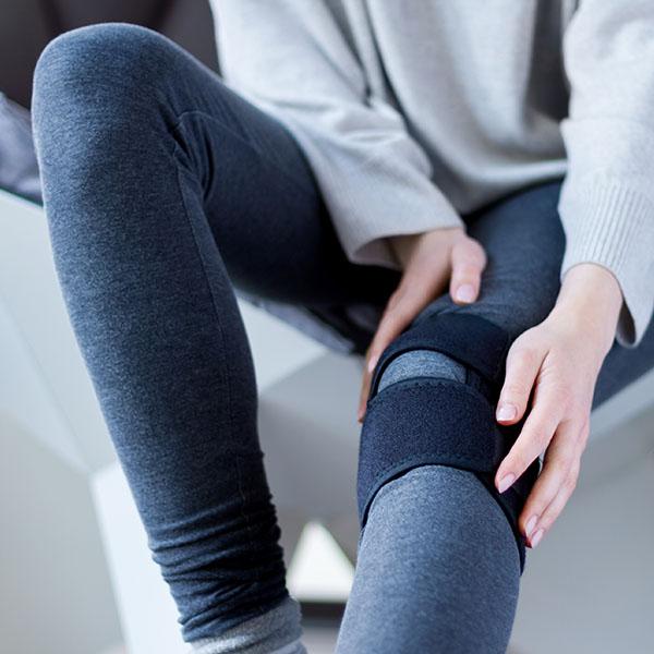 Frau mit Knie Orthese