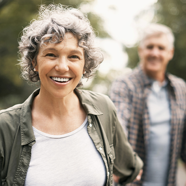 Frau spaziert fröhlich mit Mann durch Park