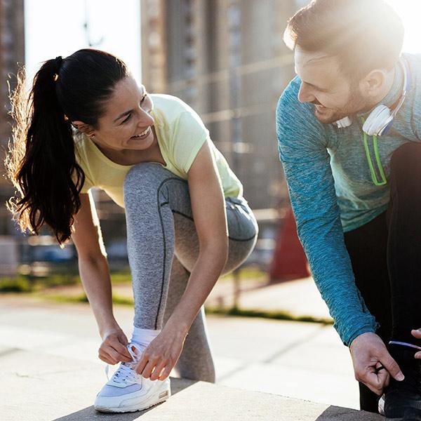 Frau und Mann schnüren Joggingschuhe