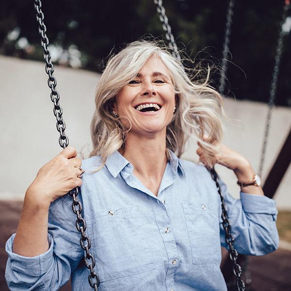 Frau lacht auf Schaukel