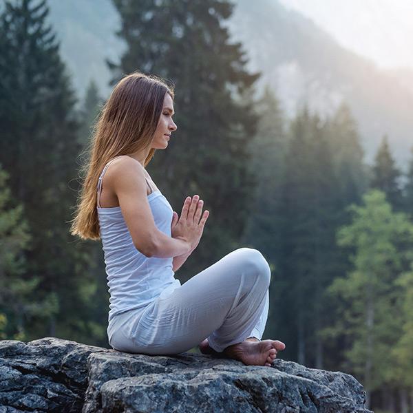 Frau im Yogasitz im Freien