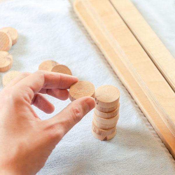 Hand greift nach Holzscheiben
