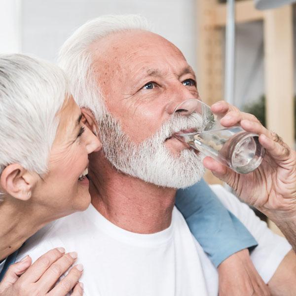 Älterer Mann trinkt beschwerdefrei aus Wasserglas und Frau freut sich