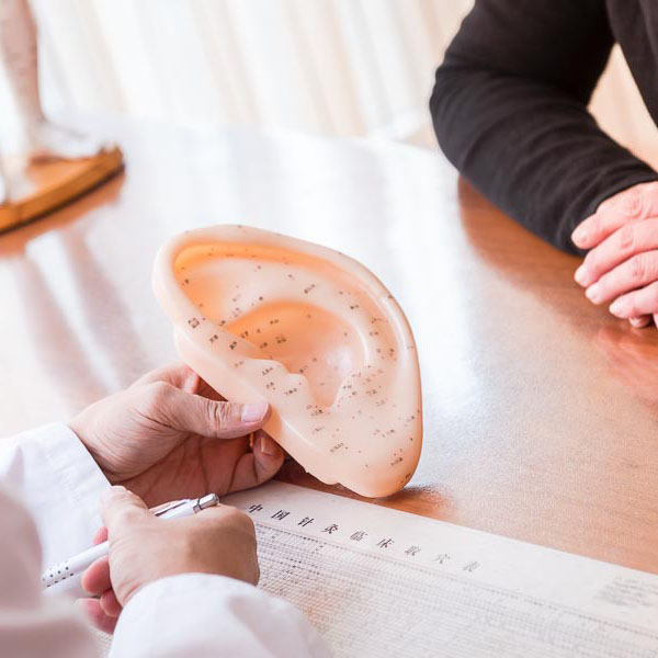 TCM Arzt erklärt Akupunkturpunkte am Ohr